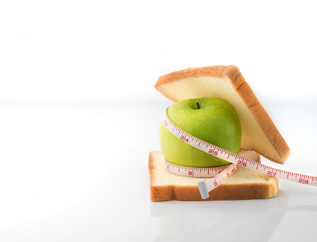 Measuring tape wrapped around a green apple with slice of white bread as a symbol of diet Premium Photo