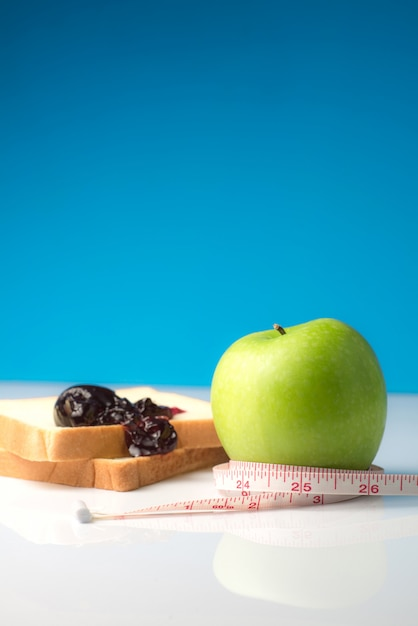 Measuring tape wrapped around a green apple with slice of white bread Premium Photo