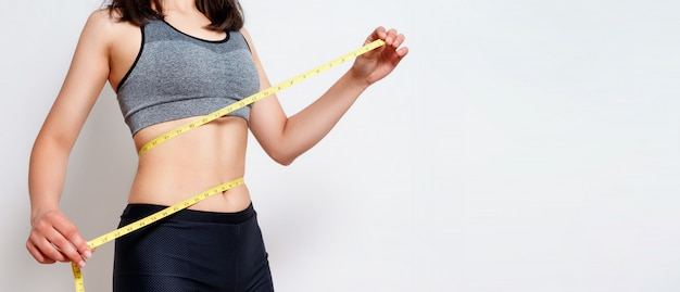 Measuring waist with a tape. fit and healthy woman on gray isolated Premium Photo