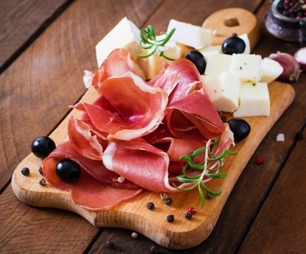 Meat appetizer on a plate on old wooden background Free Photo