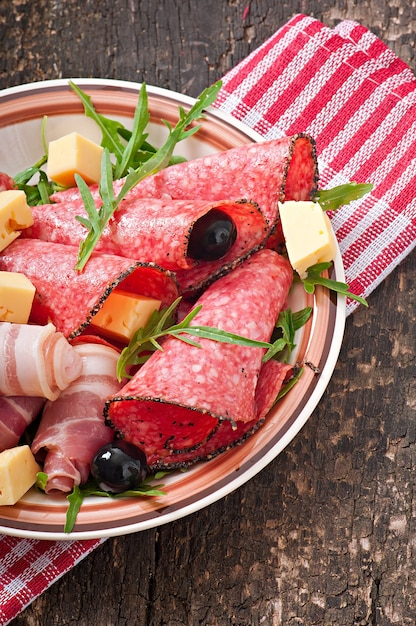Meat appetizer on a plate on old wooden surface Premium Photo