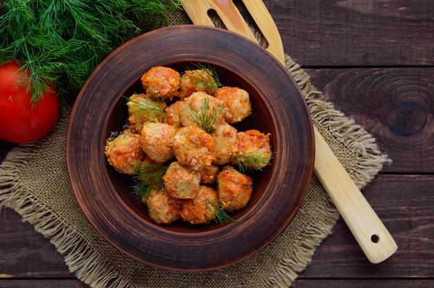 Мясные шарики с зеленью в глиняной миске. вид сверху Premium Фотографии