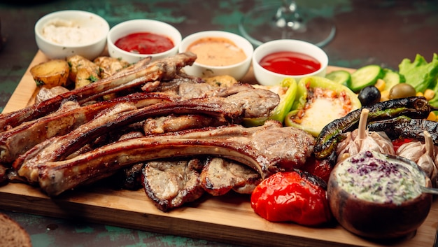 Meat barbecue with grilled vegetables and variety of sauces on a wooden platter. Free Photo