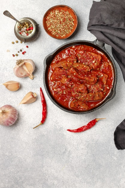 Meat (beef) stewed in tomato sauce with garlic and spices. goulash Premium Photo
