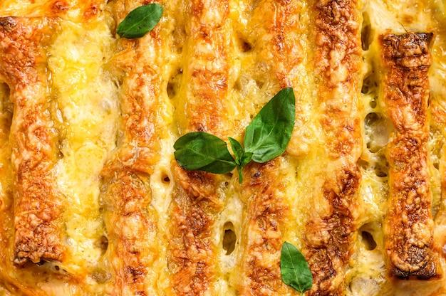 Мясные каннеллони с томатным соусом и сыром. итальянская кухня. серый фон вид сверху Premium Фотографии