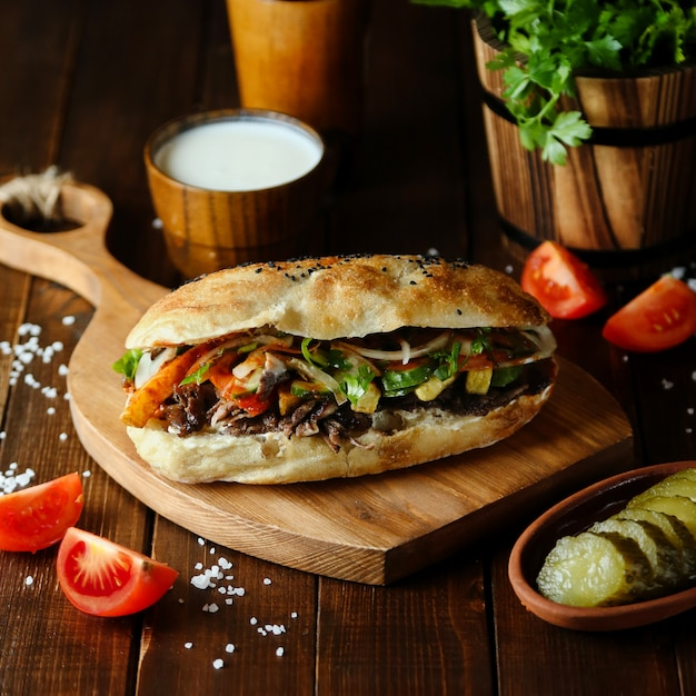Meat doner in the bread on wooden board Free Photo