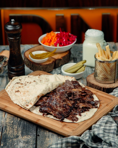 Meat doner in lavash with marinated pickles and french fries. Free Photo