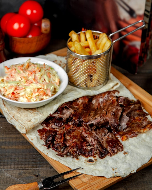 Meat doner with french fries on wooden board Free Photo