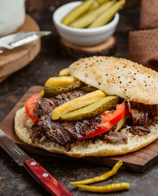 Meat doner with marinated pickels and tomato in bread. Free Photo