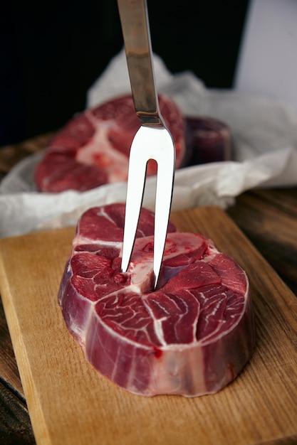 Forchetta di carne in bistecca di angus. primo piano sulla tavola di legno, davanti alle bistecche sfocate. Foto Gratuite