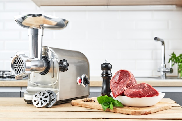 Meat grinder with fresh meat on wooden table in kitchen interior Premium Photo