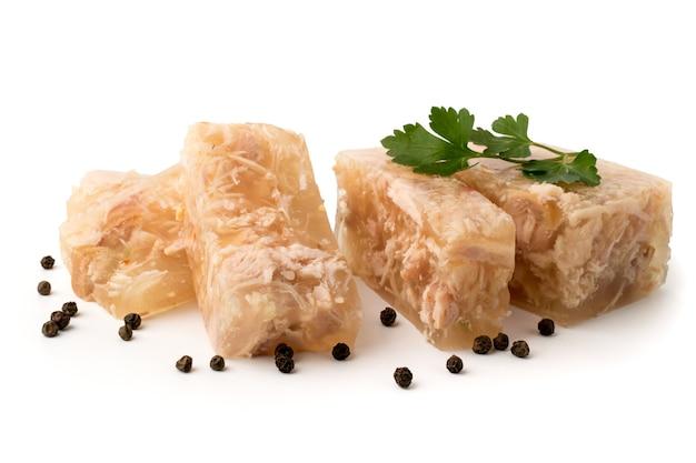 Мясное желе, нарезанное ломтиками с листьями петрушки и черным перцем на белом, крупным планом. Premium Фотографии