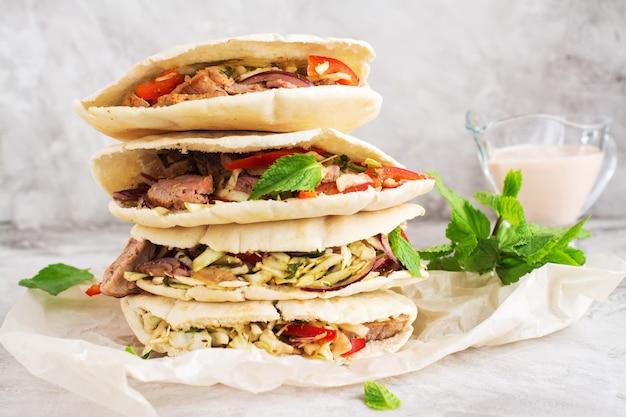 Meat pita bread with yogurt sauce and mint leaves Premium Photo