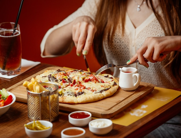 Meat pizza with cheese and vegetables on wooden board Free Photo