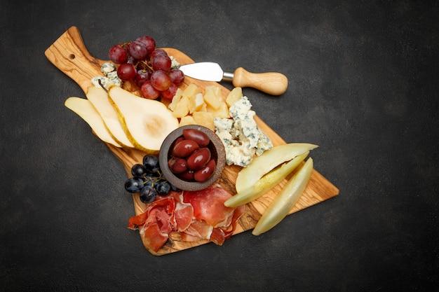 Мясная тарелка закуска закуска - ветчина прошутто, сыр с плесенью, дыня, виноград, оливки Premium Фотографии