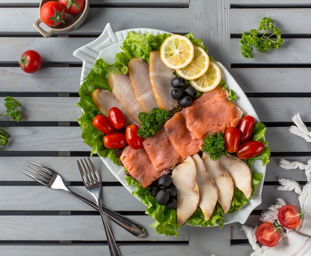 Meat plate with olives dogwood and lemon slices Free Photo