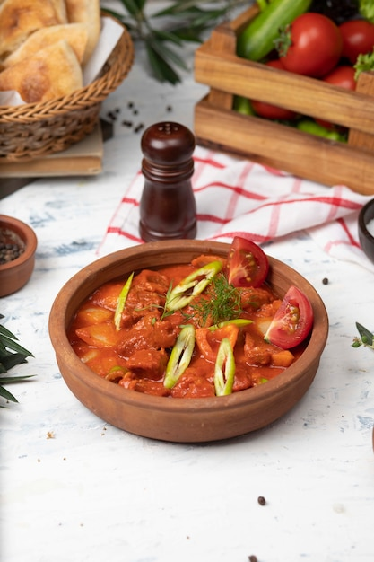 Meat potato stew with tomato sauce and pepper in pottery bowl. Free Photo