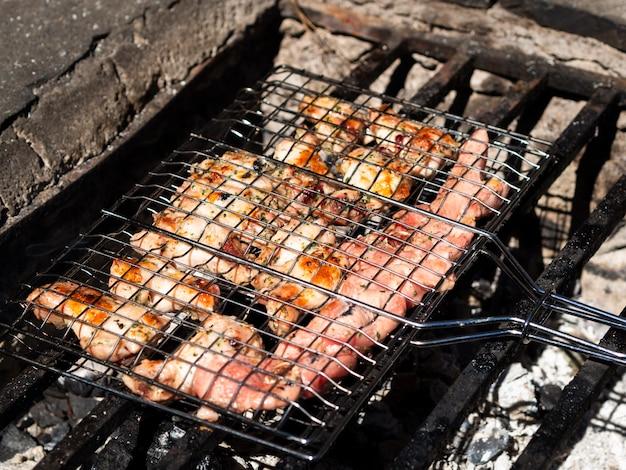 Meat roasting on rack in open fire Free Photo