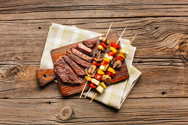 Meat skewer and fried steak slice on wooden cutting board Free Photo