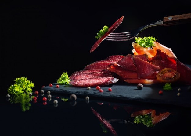 Meat sliced with greens on a black background Premium Photo