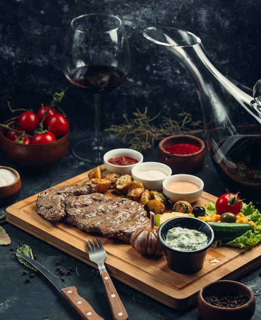 Meat steak with vegetables and variety of sauces on a wooden board. Free Photo