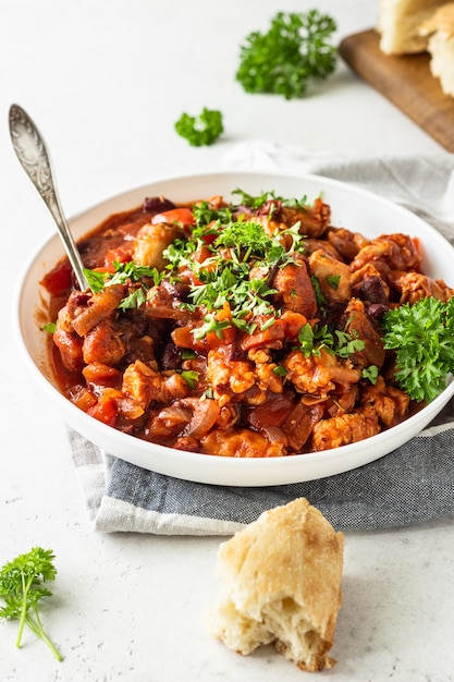 Meat stew with red beans, bell pepper and onion in tomato sauce in a white plate over light grey slate Premium Photo