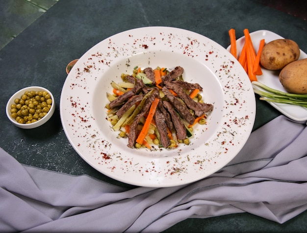 Meat and vegetable salad in the white plate. Free Photo