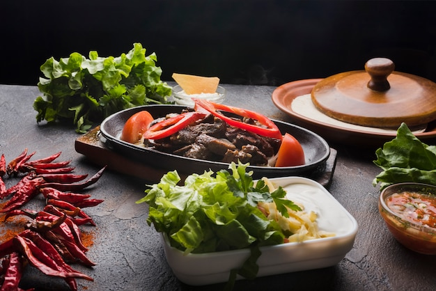 Meat, vegetables and appetizer on wooden table Free Photo