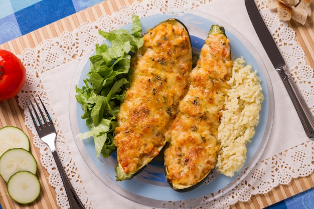 Meat and vegetables zucchini halves with rice and green salad. Premium Photo