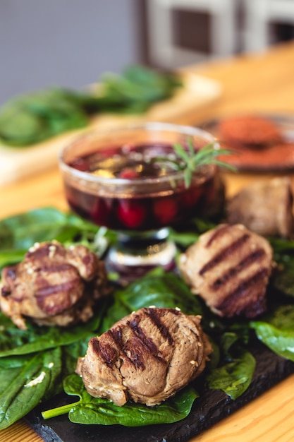 Meat with fresh herbs and cherry sauce, ready to eat. Premium Photo