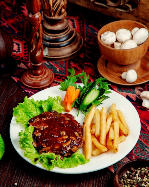 Meat with mushrooms in sauce and french fries Free Photo