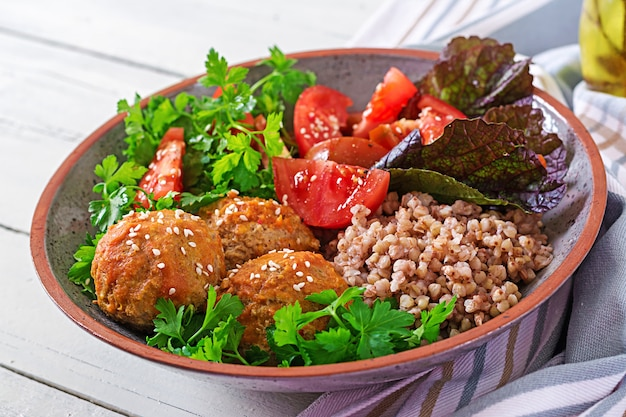 Meatballs, salad of tomatoes and buckwheat porridge on white wooden table. healthy food. diet meal. buddha bowl. Free Photo