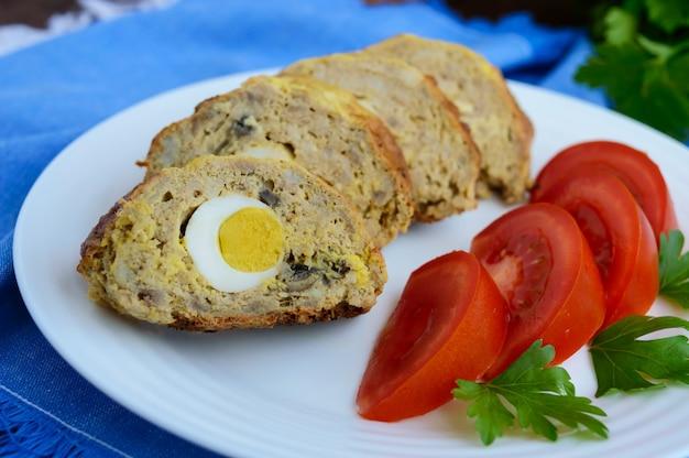 Мясной рулет с грибами и вареным яйцом. Premium Фотографии