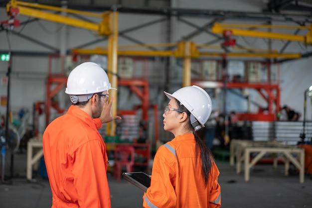 工場で話しているメカニックと女性エンジニア Premium写真