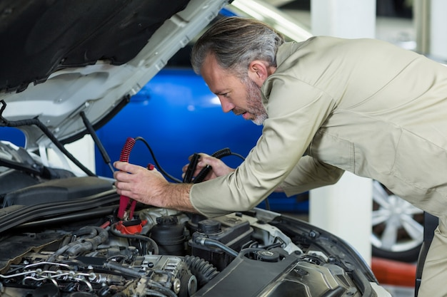 Mechanic attaching jumper cables to car battery Free Photo