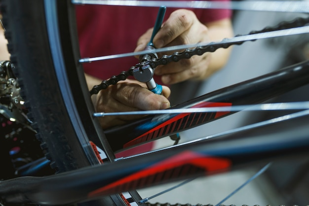 Mechanic in a bicycle repair shop fixing the chain of a bike Premium Photo