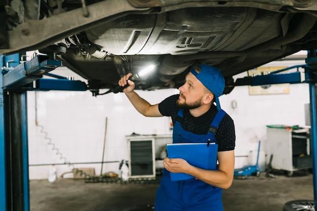 Mechanic checking bottom of car Free Photo
