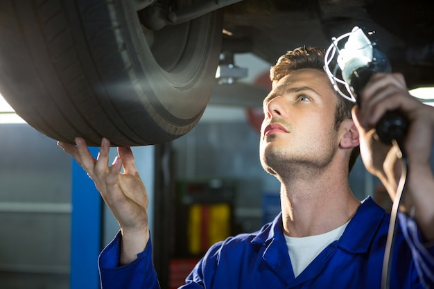 Mechanic examining car tyre using flashlight Free Photo