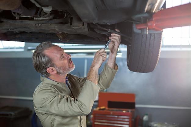 Mechanic examining car wheel brake disc Free Photo