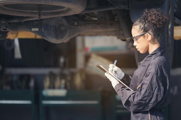 Mechanic examining underside at car service, auto repair service. Premium Photo