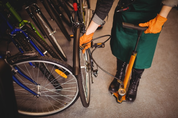 Mechanic filling air into bicycle tire with air pump Free Photo