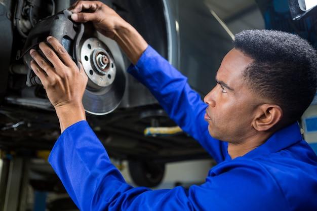 Mechanic fixing car brake Free Photo