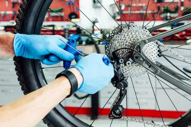 Механик, фиксирующий переключение передач велосипеда в мастерской Premium Фотографии