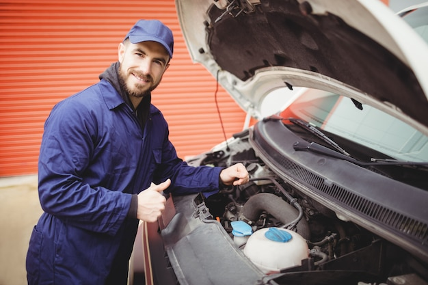 Mechanic fixing  a van with thumbs up Premium Photo