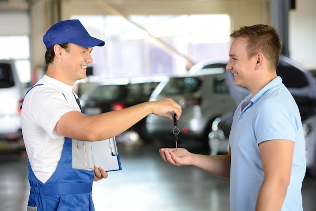 Mechanic giving car key to a client in a garage. Premium Photo