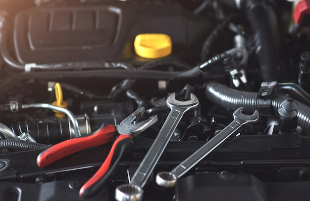 Mechanic hand checking and fixing a broken car in car service garage. Free Photo
