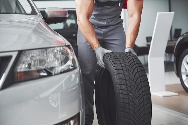 수리 차고에서 타이어 타이어를 들고 정비공. 겨울 및 여름 타이어 교체. 무료 사진