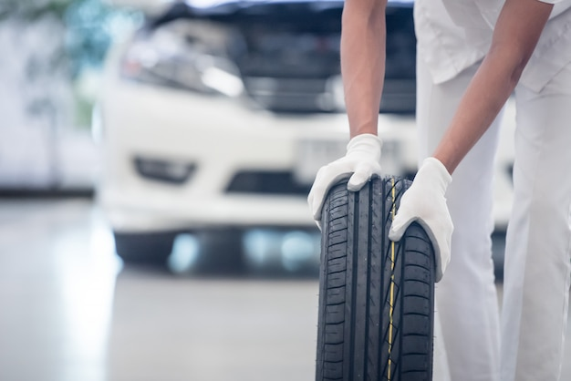 Mechanic holding a tire tire at the repair garage. replacement of winter and summer tires. Premium Photo
