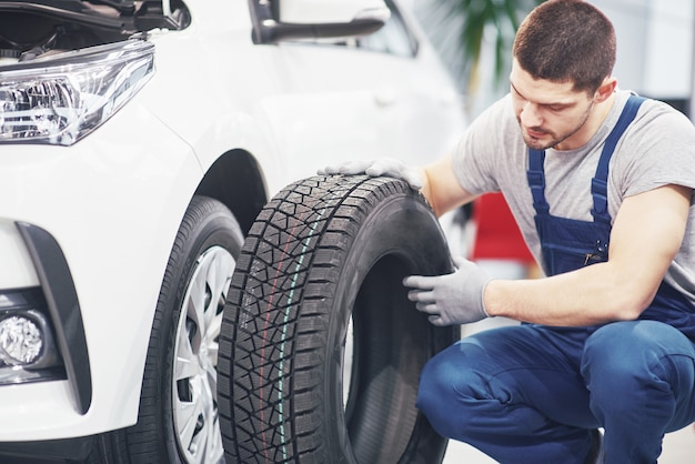 Meccanico che tiene una gomma al garage di riparazione. sostituzione di pneumatici invernali ed estivi Foto Gratuite