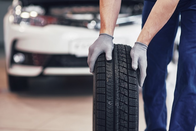 Mechanic holding a tire tire at the repair garage. replacement of winter and summer tires Free Photo